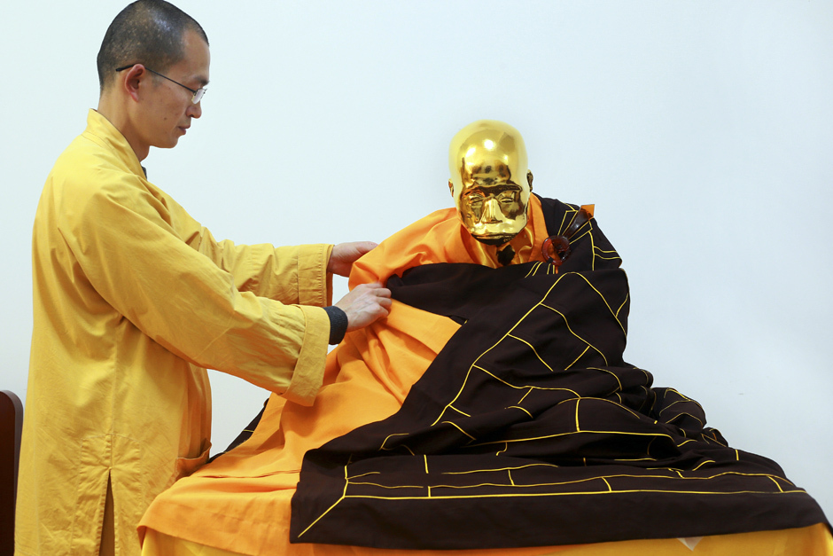 In this photo taken April 16, 2016, abbot Zhen Yu places a robe on the mummified body of revered Buddhist monk Fu Hou in Quanzhou city in southeastern China's Fujian province. The monk, who died in 2012 at the age of 94, was prepared for mummification by his temple to commemorate his devotion to Buddhism. The mummifed remains were then treated and covered in gold leaf, a practice reserved for holy men in some areas with strong Buddhist traditions. (Chinatopix via AP) CHINA OUT ORG XMIT: XHG805